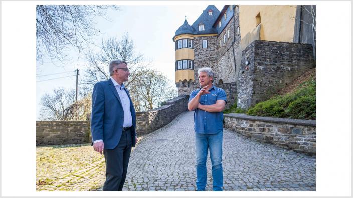 Das Foto zeigt Bürgermeisterkandidat Michael Conrad und Herbergsvater Jürgen Hof auf der Freusburg im Kirchner Ortsteil Freusburg.